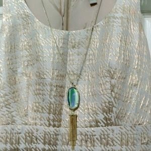 A long necklace in gold with dichoric glass.